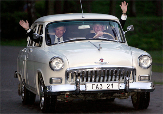 "RUSSIE, ODINSOVSKY: US President George W. Bush (R) and Russian President Vladimir Putin wave as the two presidents go for a ride in Putin's 1956 Volga before dinner 08 May 2005 at the his residence outside of Moscow. Bush hailed Russia's ""bravery and sacrifice"" in defeating Nazism, as he met Putin ahead of ceremonies marking the 60th anniversary of the end of World War II. Bush, who the previous day criticized the decades-long Soviet occupation of central Europe, said he was looking forward to the 09 May ceremony on Moscow's Red Square, to be attended by over 50 national leaders. (Tim Sloan/Agence France-Presse)"