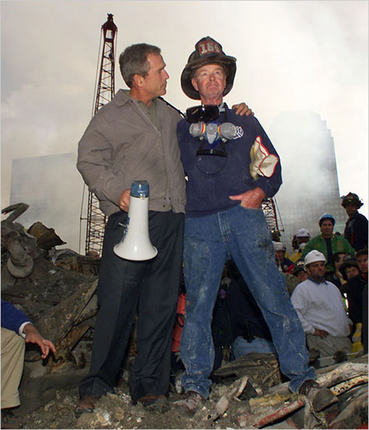 As rescue efforts continue in the rubble of the World Trade Center, President Bush puts his arms around firefighter Bob Beck while standing in front of the World Trade Center debris during a tour of the devastation, Friday September 14, 2001. Bush is standing on a burned fire truck. Mayor Rudolph Giuliani said 4,763 people have been reported missing in the devastation of the World Trade Center. (Doug Mills/The Associated Press)